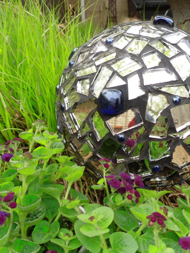 A bowling ball makes a great base for a garden mosaic gazing ball. Broken mirror pieces and blue marbles glued-on and grouted do the trick. Leave a hole open to prop the ball on a dowell or stake in the garden.